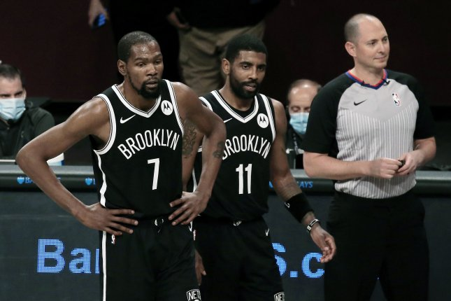 Brooklyn Nets forward Kevin Durant (7) and guard Kyrie Irving (11) return to the court following a timeout during the first half of a preseason game against the Washington Wizards on Sunday at Barclays Center in Brooklyn. Photo by Peter Foley/EPA-EFE