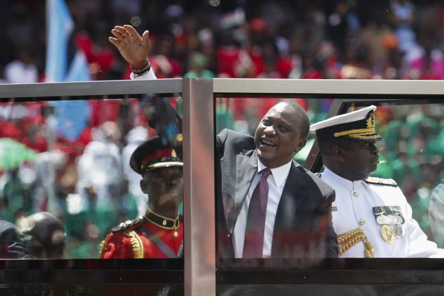 Kenyan President Uhuru Kenyatta greets the crowd from a convoy upon arriving at his swearing-in ceremony at a stadium in Nairobi, Kenya, on November 28. Despite a warning by the attorney general, the National Super Alliance says opposition candidate Raila Odinga will be sworn in Tuesday. Photo by Dai Kurokawa/EPA-EFE