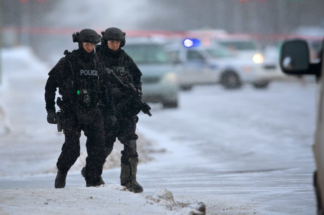 Members of a Quebec police SWAT team patrol near the scene of a shooting at a Quebec City mosque, on January 30, 2017. The attack killed six people and injured nearly two dozen. File Photo by Andre Pichette/EPA