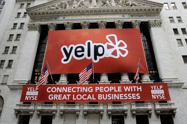 A sign for the online consumer review site Yelp hangs on the front of the New York Stock Exchange ahead of its 2012 IPO. On Friday, the company announced it would begin allowing users to search for businesses that have a gender-neutral bathroom policy in solidarity with transgender rights. File Photo by Justin Lane/EPA