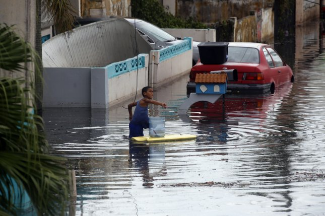A child plays in a flooded street in the aftermath of Hurricane Maria, in Catano, Puerto Rico. Hurricane Maria, the most powerful storm to hit Puerto Rico in nearly a century, has knocked out power to all of the island's 3 million residents. Photo by Thais Llorca/EPA-EFE