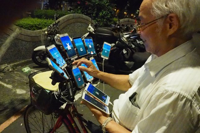 Chen San-yuan, a 69-year-old Feng Shui Master, uses 11 cellphones to catch Pokemon in a park in New Taipei City, Taiwan, on Aug. 8, 2018. Photo by David Chang/EPA-EFE