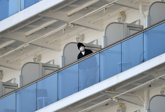 A passenger of the Diamond Princess cruise ship stands on cabin balconies near the Daikoku Pier Cruise Terminal in Yokohama, Japan, on Tuesday. Photo by Franck Robichon/EPA-EFE