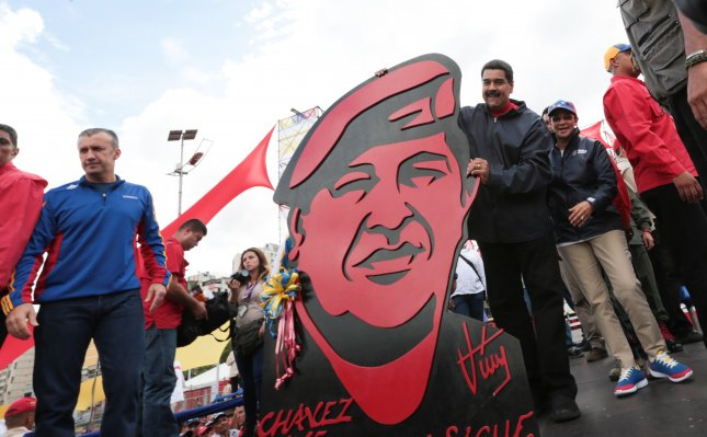 Venezuelan President Nicolas Maduro (R) holding an image depicting former President Hugo Chavez, next to his wife Cilia Flores during a demonstration in Caracas. Photo by Mira Flores/EPA/Handout