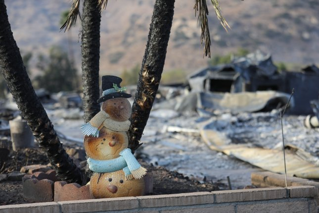 A charred snowman holiday display looks out over mobile homes consumed by the Lilac wildfire in Fallbrook, Calif., in Dec. 2017. The fire swept through the area, destroying dozens of trailer homes in the retirement community. Photo by Eugene Garcia/EPA-EFE