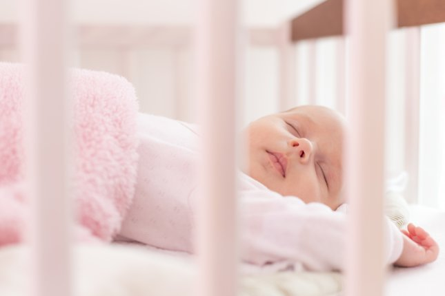 Baby sleeping in crib. File photo by OndroM/Shutterstock