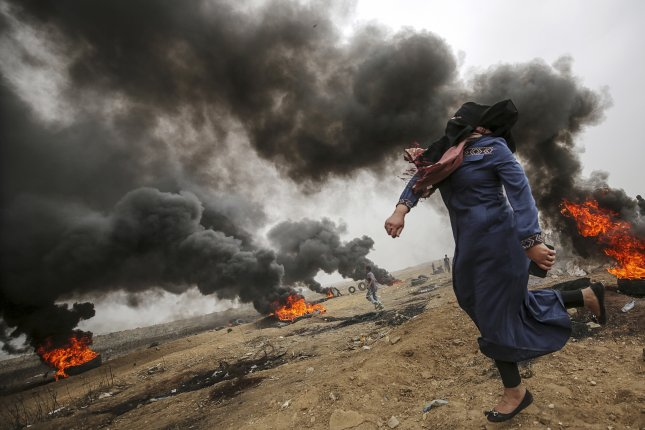 A female Palestinian protester throws stones on Friday during clashes near the border with Israel in the eastern Gaza Strip. On Saturday, an explosion in the central Gaza Strip killed at least six members of Hamas' military. Photo by Mohammed Saber/EPA-EFE
