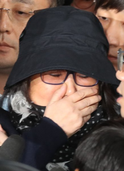 Choi Soon-sil, who is suspected of having meddled in state affairs and peddled influence on various state projects by exploiting her decades-long friendship with President Park Geun-hye, puts a hand over her mouth while entering the Seoul Central District Prosecution Office in Seoul for questioning on Monday. Photo by Yonhap