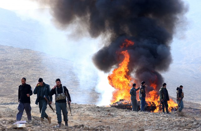 Afghan police stand guard as the authorities burn illegal drugs in Kabul, Afghanistan, on December 20, 2016, that were seized during different operations. On Monday, the Ministry of Interior announced Afghan National Defense and Security Forces destroyed six heroin labs in Helmand province in southern Afghanistan. Photo by Hedayatullah Amid/EPA