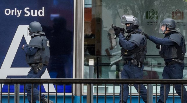 Armed police special intervention units move into position at Orly airport near Paris on Saturday. According to news reports a person has been shot by Operation Sentinelle anti-terror patrol soldiers at Orly Airport after trying to snatch a soldier's weapon. Photos by Christophe Petit Tesson/EPA