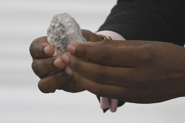 A 1,098-carat gem diamond unearthed by the Botswana Government and De Beers joint venture mining company Debswana, is shown to President Mokgweetsi Masisi on Wednesday at the Botswana State House. Photo by STR/EPA-EFE