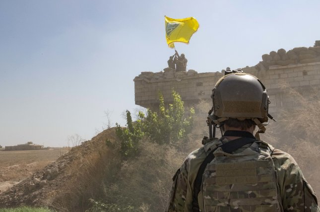 A U.S. soldier oversees members of the Syrian Democratic Forces as they demolish a YPG (People's Protection Units, a mainly-Kurdish militia in Syria) fortification and raise a Tal Abyad Military Council flag over the outpost as part of the security mechanism zone agreement in  Syria on September 21. Photo by U.S. Army Staff Sgt. Andrew Goed/EPA-EFE