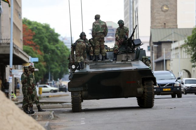Zimbabwe soldiers stand on and next to an armored vehicle in the central district of Harare, Zimbabwe, on Thursday -- a day after the Zimbabwe National Army took control of the government from President Robert Mugabe. Photo by Aaron Ufumeli/EPA-EFE