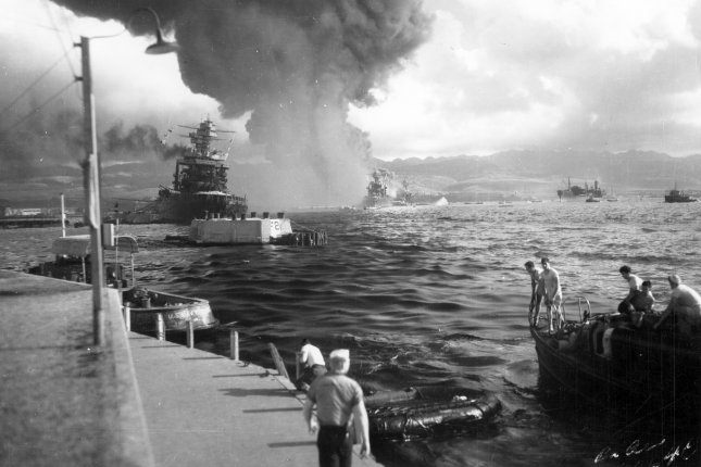 A view looking down Battleship Row at the Pearl Harbor naval base from Ford Island Naval Air Station, shortly after the Japanese torpedo plane attack on December 7, 1941. USS California is at left, listing to port after receiving two torpedo hits. In the center are USS Maryland with the capsized USS Oklahoma alongside. Most smoke is from USS Arizona. File Photo by U.S. Navy
