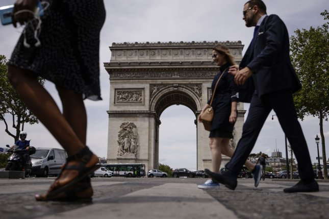 People not wearing protective face masks walk past the Arc of Triomphe in Paris on June 17. File photo by Yoan Vala/ EPA-EFE