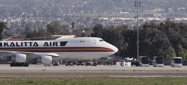 Americans evacuated from Wuhan, China, during the coronavirus outbreak deplane the Kalitta Air Boeing 747-400 freighter and are shuttled onto waiting busses at the March Air Reserve Base in Riverside, California, on Jan. 29. Photo by Etienne Laurent/EPA-EFE