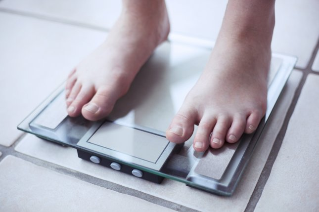 obese scale obesity weight feet bathroom. Photo by Tiago Zr/Shutterstock