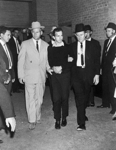 Guards escort Lee Harvey Oswald in the basement of the Dallas police station two days after his arrest in conjunction with the assassination of President Kennedy in Dallas, Texas on November 24, 1963. Moments later Oswald was shot by Jack Ruby. Photo by Frank Johnston/UPI