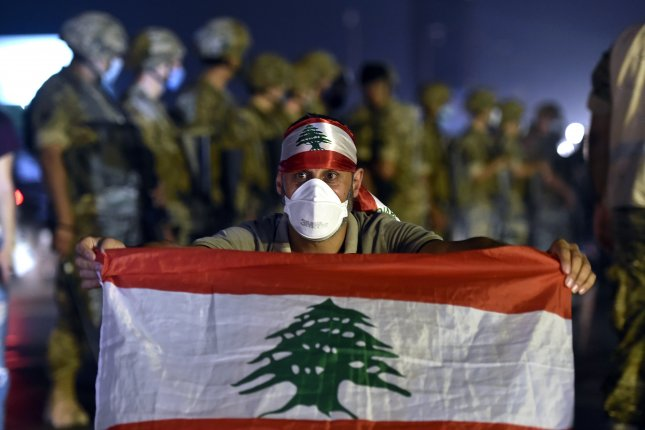 An anti-government protester poses with a national flag in front of the Lebanese army soldiers during a protest to demand a change of the sectarian system and finding solutions to the economic crisis in the Jal El Dib area north of in Beirut, Lebanon on Sunday. Photo by Wael Hamzeh/EPA-EFE