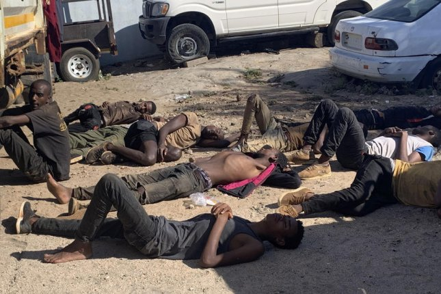 Survivors from the container rest on the ground Tuesday after they were found alive inside with 64 dead, in Tete province, Mozambique. Photo by EPA-EFE