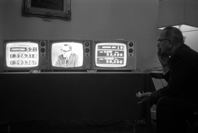 President Lyndon B. Johnson watches the television sets in his room at the Driskill Hotel in Austin, Texas, as elections returns are reported on Nov. 3, 1964. Johnson would win the presidency in a landslide victory over Senator Barry Goldwater of Arizona. File Photo by LBJ Library/UPI