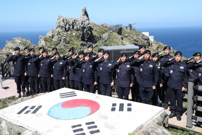 Coast guard members stationed on South Korea's easternmost Dokdo Islets salute the national flag while resolving to uphold the islets' defense. Photo by Yonhap.