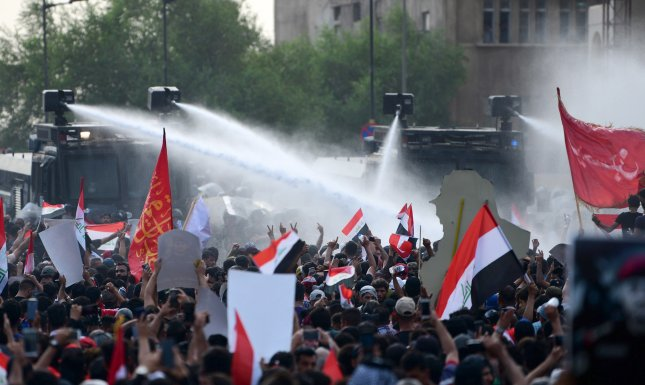 Iraqi anti-riot policemen use water cannons to block Iraqi protestors during a demonstration at al-Tahrir square in Baghdad on Tuesday. Murtaja Lateef/EPA-EFE