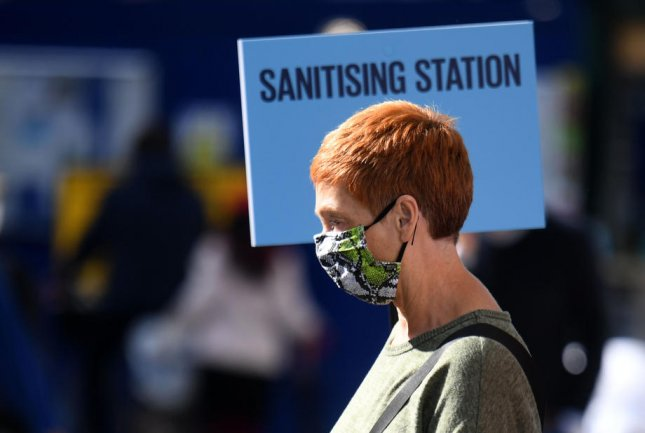 A woman passes a sanitizing station for cleaning of hands in Oxford Street in London, Britain. File Photo by Neil Hall/EPA-EFE