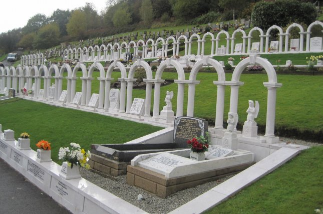 On October 21, 1966, an avalanche of coal slag cascaded down a Welsh mountainside, burying a school and killing 148 people, mostly young students, whose graves are marked with a series of arches. File Photo by Llywelyn2000/Wikimedia