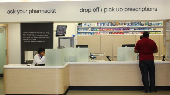 Pharmacists assist a customer at the counter and on the phone at a pharmacy in Washington, DC. (File/UPI/Billie Jean Shaw)