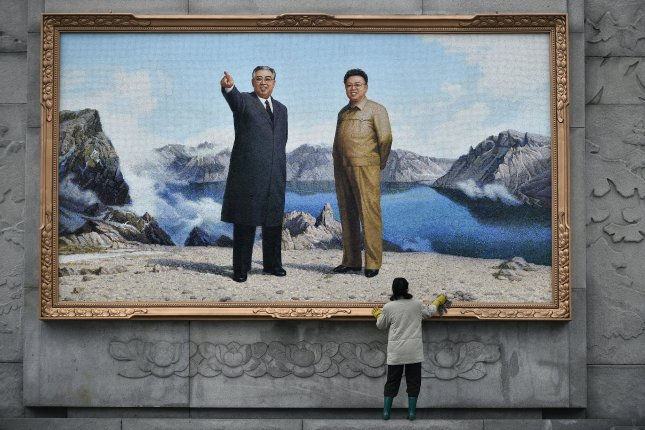 A woman cleans the frame of a large mosaic representing former leaders Kim Il Sung (L) and Kim Jong Il at the Mansudae Art Studio in Pyongyang, North Korea. File Photo by Franck Robichon/EPA