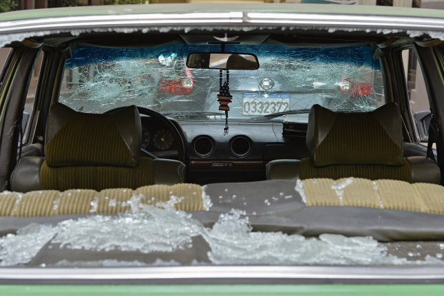 A damaged car is seen after a night of clashes between supporters of Hezbollah and Amal Movement with anti-government protesters in Beirut, Lebanon on Monday. Photo by Wael Hamzeh/EPA-EFE