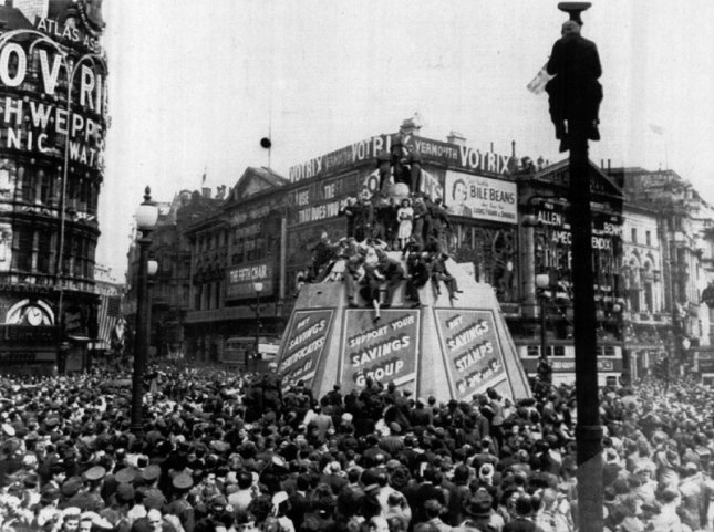 People jam Piccadilly Circus during celebration of V-E Day on May 8, 1945 in London England. Some perch atop Eros Statue and one person has climbed a post. March 8, 2015 marks the 70th anniversary of the allied victory over axis forces in Europe. File photo by UPI