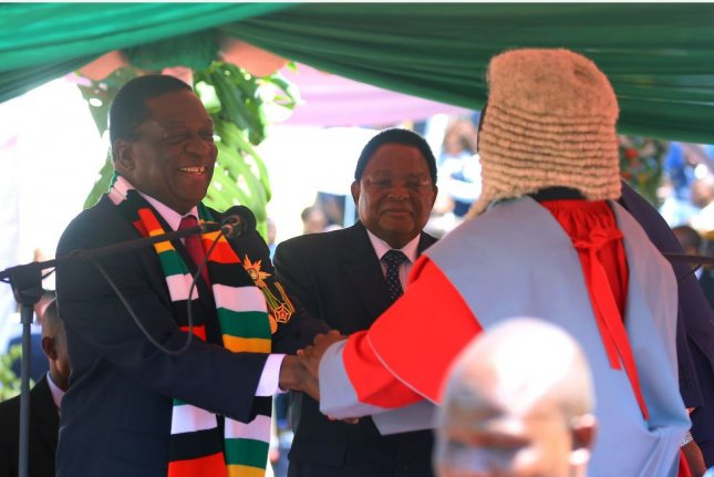 Emmerson Mnangagwa (L) shakes hands with Zimbabwe's Chief Justice Luke Malaba (R) after being sworn in Sunday as president of Zimbabwe at the National Sports Stadium in Harare. Photo by Aaron Umeli/EPA