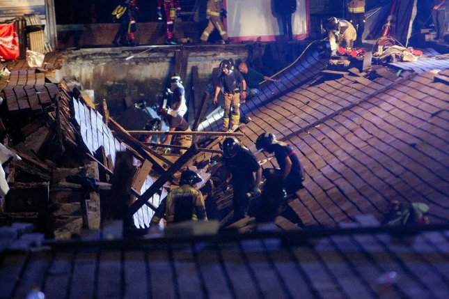 Firefighters search for victims after a wooden boardwalk collapsed during a concert in Vigo, Spain, late Sunday. Photo by Salvador Sas/EPA-EFE