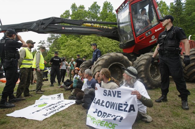 Polish police watch activists protest in a village in the Bialowieza Forest on June 8. Thursday, the European Commission called on Poland to immediately suspend logging in the forest. File Photo by Artur Resko/EPA