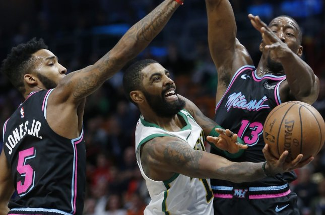 Boston Celtics guard Kyrie Irving (C) is defended by Miami Heat guard Derrick Jones Jr. (L) and forward Bam Adebayo (R) during the NBA basketball game between the Boston Celtics and Miami Heat on Thursday at the AmericanAirlines Arena in Miami. Photo by Rhona Wise/EPA-EFE