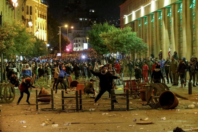 Protesters throw stones at riot police during clashes in central Beirut, Lebanon, on December 15. The uprising has been going on for a year, with no government reform in sight. File Photo by Nabil Mounzer/EPA-EFE