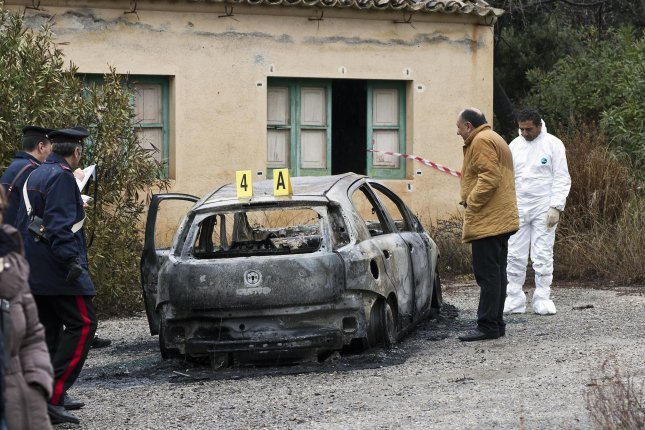 Italian authorities investigate a burned vehicle, where three people were found dead, in Cassano allo Ionio, Calabria province, Italy, on January 19, 2014. Officials said theNdrangheta syndicate was behind the killings. File Photo by Francesco Arena/EPA