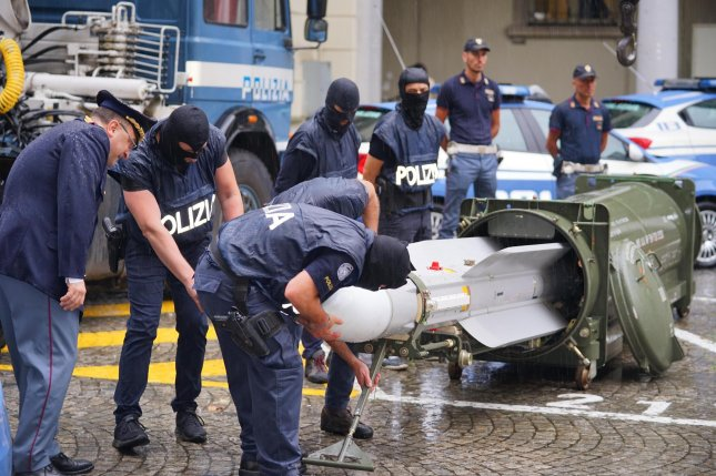 Special forces officers inspect an air-to-air missile seized during an operation against the extreme right in Turin, Italy, on Monday. Photo by Tina Romano/EPA-EFE