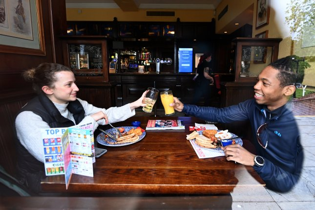 Patrons raise their glasses on Monday at the Fox on the Hill pub in London, Britain, on the first day of significantly relaxed coronavirus restrictions, including those that barred large social gatherings indoors and outdoors. Photo by Andy Rain/EPA-EFE