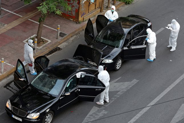 Police investigators inspect a Mercedes car and an escort vehicle of former Greek Prime Minister Lucas Papademos after an explosion caused by a letter bomb attack in central Athens, Greece, on May 25. A suspect was arrested Saturday. Photo by Simela Pantzartzi/EPA