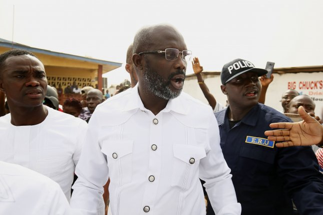 Former international soccer star George Weah, center, was inaugurated as Liberia's president in a Monrovia stadium on Monday. Photo by Ahmed Jallanzo/EPA-EFE