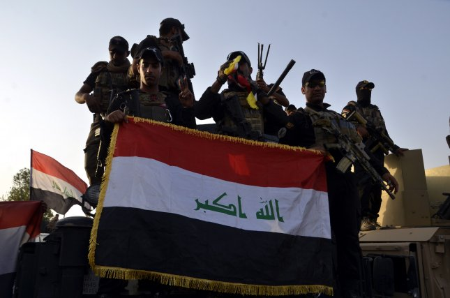Iraqi soldiers held up the Iraqi national flag in central Mosul, northern Iraq, in July 2017. On Thursday, Syrian Democratic Forces handed over 150 Islamic State fighters it had detained to the Iraqi army. File Photo by STR/EPA-EFE