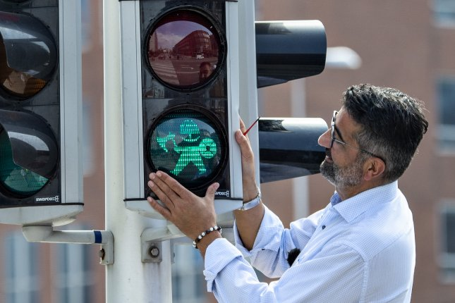 Local official Buenyamin Simsek of Aarhus, Denmark, replaces the first of a planned 17 pedestrian signals to give tribute to the city's Viking Monday. Photo by Henning Bagger/EPA-EFE