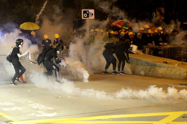 Police officers deploy tear gas against demonstrators in Hong Kong on August 3. Photo by Jerome Favre/EPA-EFE