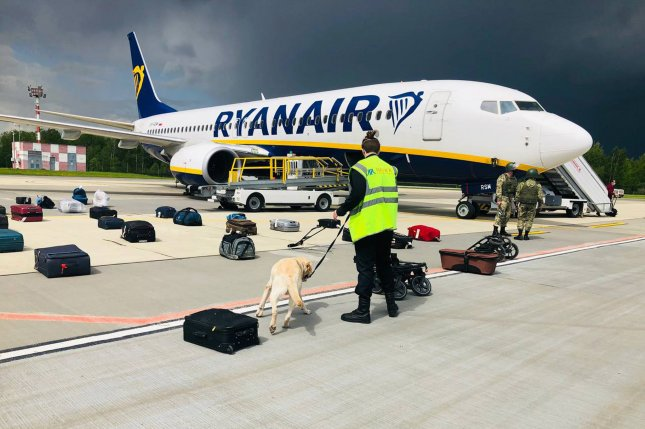 A security guard with a sniffer dog checked the luggage of passengers in front of a Ryanair flight that forced to land in Minsk, Belarus, on May 23. File photo by EPA-EFE/ONLINER.BY