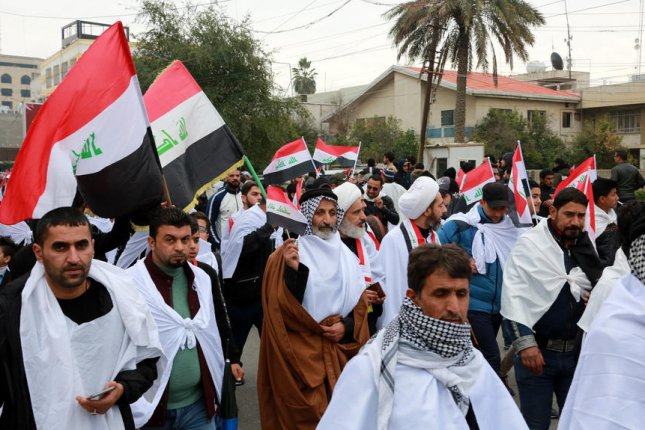 Activists chant slogans and carry the Iraqi national flag on Friday during a mass demonstration in Baghdad, Iraq, that called for the immediate withdrawal of U.S. military forces. Photo by Ahmed Jalil/EPA-EFE