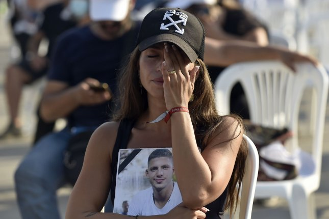 A relative of a victim of the August 4, 2020, Beirut port explosion in Lebanon carries his portrait as she attends a mass held to commemorate the first year anniversary of the blast. Photo by Wael Hamzeh/EPA-EFE