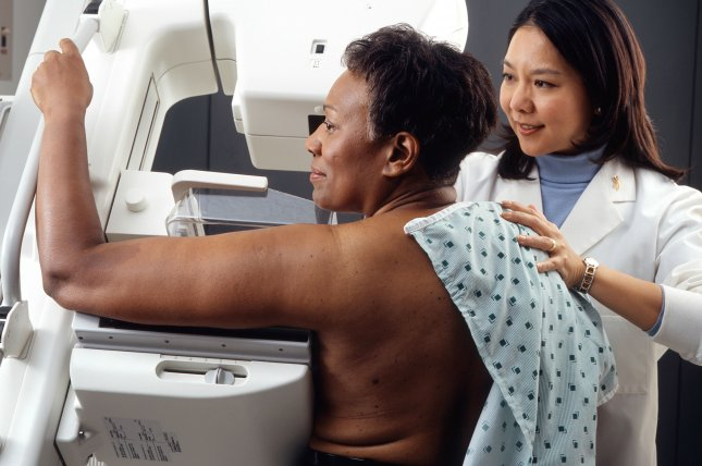 A technician positions a woman at an imaging machine to receive a mammogram. Photo by Rhoda Baer/Wikimedia Commons